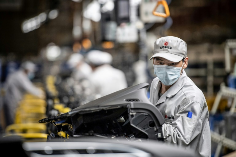 Un empleado con mascarilla trabaja en la cadena de montaje de una fábrica de automóviles, el 23 de marzo de 2020 en la ciudad china de Wuhan.