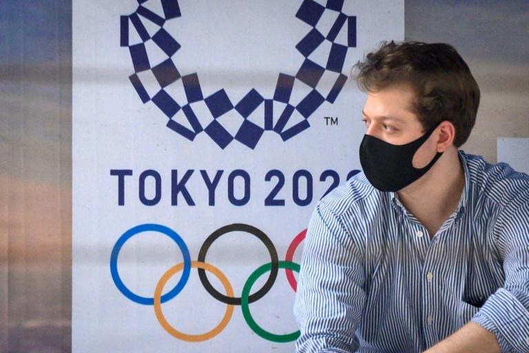 Un hombre con mascarilla protectora aguarda en una parada de autobús que expone un cartel de los Juegos Olímpicos de Tokio, el 16 de marzo de 2020 en Bangkok, la capital tailandesa.