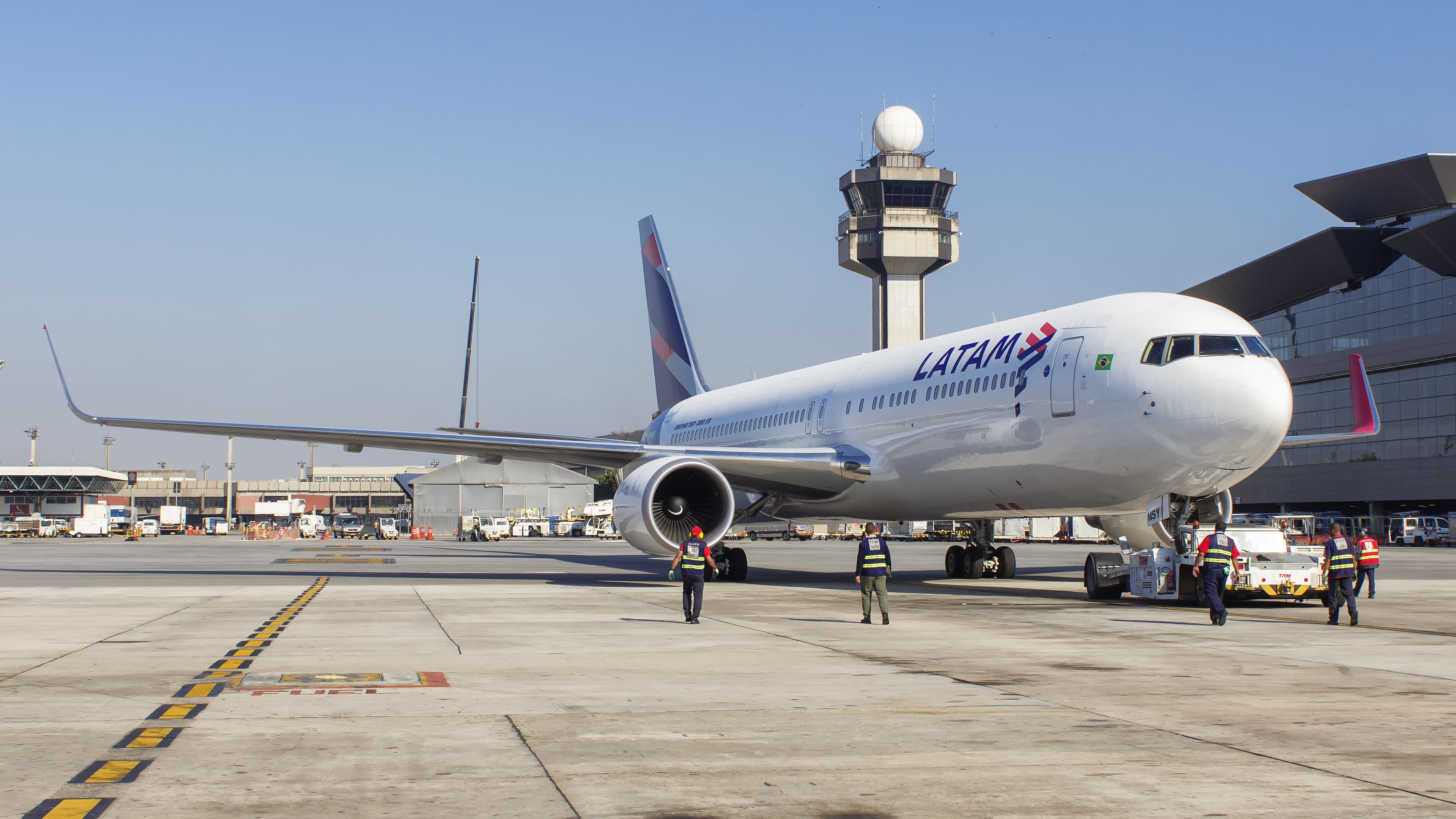 Boeing 767 of Latam Airlines push back with air traffic controller tower in background at Guarulhos International Airport in Sao Paulo Brazil