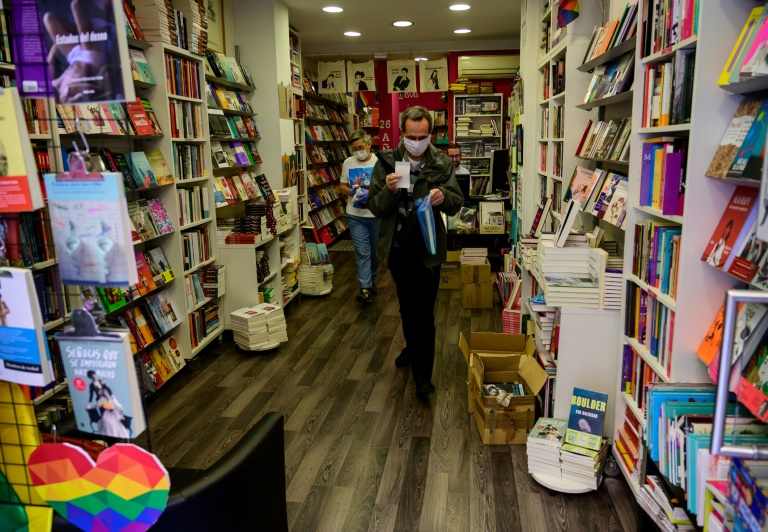 Un cliente con mascarilla sale de una librería de Madrid con un libro en el primer día de reapertura de comercios tras las restricciones impuestas por el coronavirus, el 4 de mayo de 2020 en la capital de España.