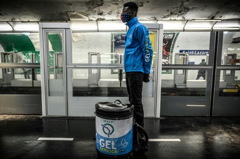 Un empleado de la administración de los transportes de París espera a los viajeros para distribuir gel hidroalcohólico en la línea 13 del metro el 14 de mayo de 2020.