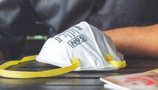 closeup N95 air filter mask. personal protective equipment in office with soft-focus and over light in the background