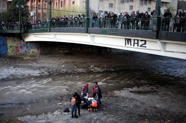 El viernes 2 de octubre, mientras se realizaban manifestaciones en el sector de Plaza Italia, un joven de 16 años fue empujado por un carabinero desde el puente Pío Nono al río Mapocho. Foto: Agencia UNO.