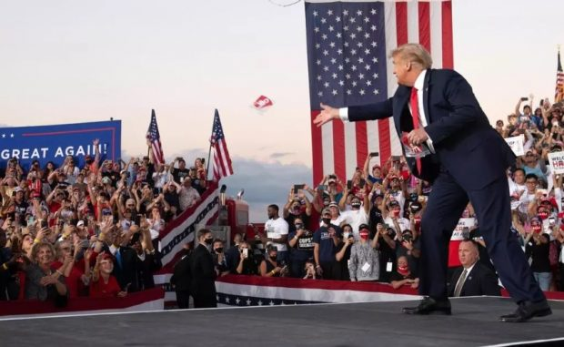 El presidente de EEUU lanza mascarillas a sus seguidores a su llegada a su primera reunión de campaña desde su infección de Covid-19 el 12 de octubre en Sanford, Florida. SAUL LOEB / AFP