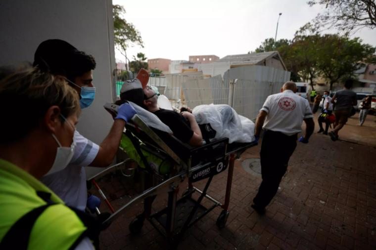 Médicos israelíes evacuan a un hombre herido después de que un cohete lanzado desde la Franja de Gaza impactara en un edificio residencial en Ashkelon, al sur de Israel el 11 de mayo de 2021. REUTERS/Amir Cohen REUTERS - AMIR COHEN