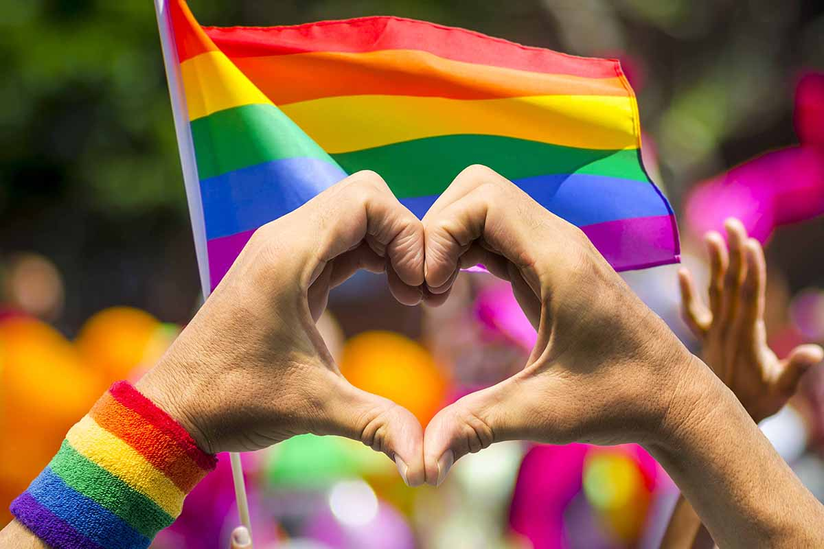 Supporting hands make heart sign and wave in front of a rainbow