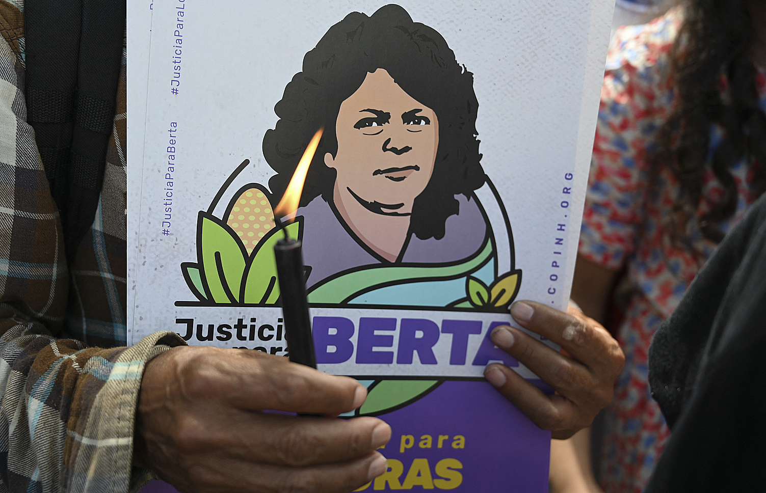 A member of the Civic Council of Popular and Indigenous Organizations of Honduras (COPINH) holds a candle while waiting for the sentence of David Castillo, president of Desarrollos Energeticos S.A (DESA), to be read, regarding the murder of Honduran environmentalist and indigenous leader Berta Caceres (in poster), in Tegucigalpa on July 5, 2021. - Castillo was found guilty. (Photo by Orlando SIERRA / AFP)
