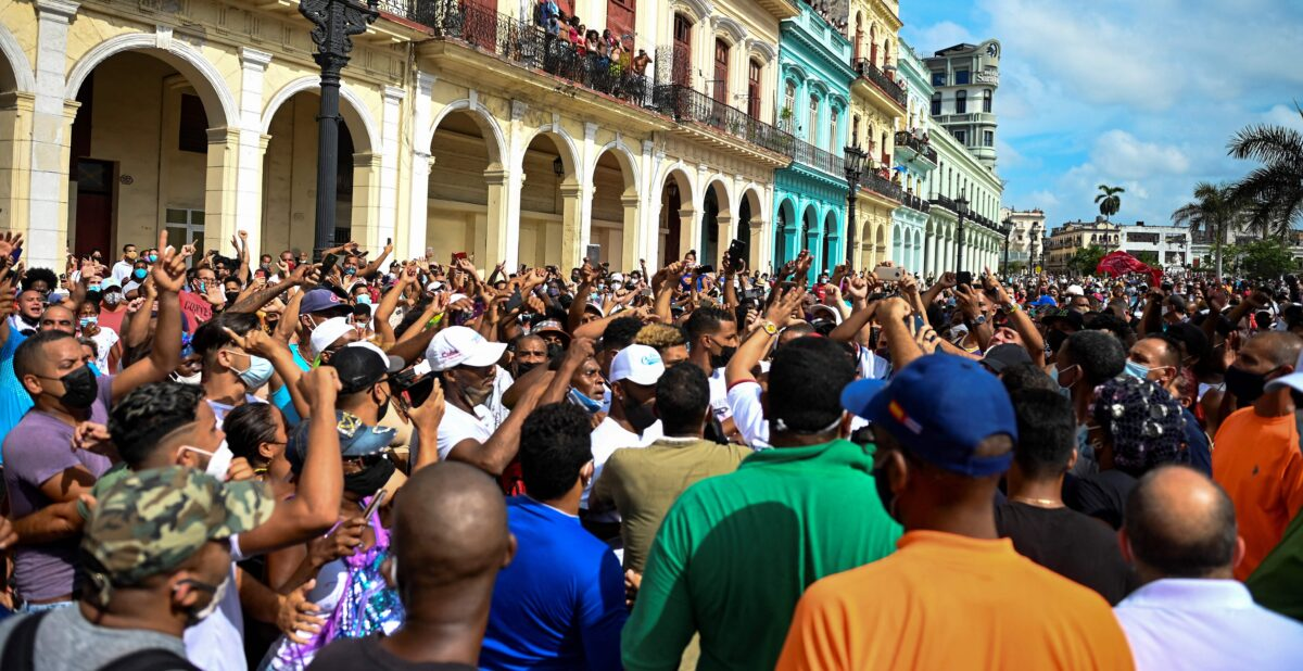"""People take part in a demonstration against the government of Cuban President Miguel Diaz-Canel in Havana, on July 11, 2021. - Thousands of Cubans took part in rare protests Sunday against the communist government, marching through a town chanting """"Down with the dictatorship"""" and """"We want liberty."""" (Photo by YAMIL LAGE / AFP) (Photo by YAMIL LAGE/AFP via Getty Images)"""