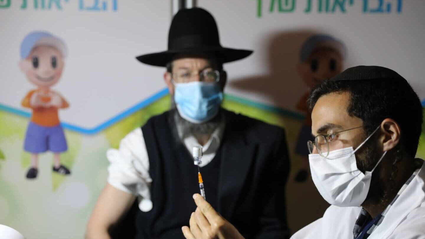 Tel Aviv (Israel), 14/01/2021.- An ultra-orthodox Jewish man receives a coronavirus COVID-19 pandemic vaccine by a male nurse in Jerusalem, Israel, 14 January 2021. Media report that Israel is on a massive nationwide COVID-19 vaccination campaign, with more than two million people already got the first dose. (Estados Unidos, Jerusalén) EFE/EPA/ABIR SULTAN